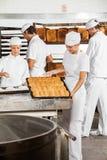 Женщина анализируя хлебы пока коллеги работая в хлебопекарне Стоковая Фотография RF