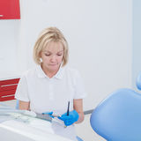 Женщина дантиста при светлые волосы сидя на стуле в зубоврачебном офисе Стоковая Фотография