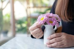Женщина аранжируя красивые розовые цветки в белой малой вазе на таблице стоковые фотографии rf