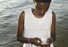 Женщина африканского происхождения используя мобильный телефон морем стоковое фото