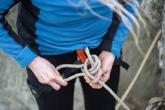 Женщина альпиниста в ремнях безопасности связывая веревочку в узле булиня Стоковые Фотографии RF