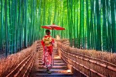 Женщина бамбукового леса азиатская нося японское традиционное кимоно на бамбуковом лесе в Киото, Японии