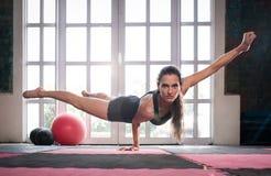 Женщина балансируя пока делающ одну руку нажимает вверх показывать прочность Стоковая Фотография RF