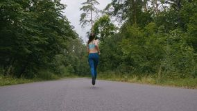 Женщина бегуна бежать и скача на дорогу в лесе в slowmotion фитнес outdoors Съемка с steadicam видеоматериал