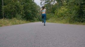 Женщина бегуна бежать на дороге в лесе в slowmotion фитнес outdoors Съемка с steadicam Концепция утра идущая видеоматериал