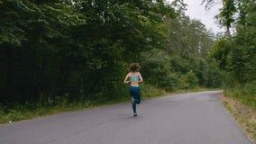 Женщина бегуна бежать на дороге в лесе в slowmotion фитнес outdoors Съемка с steadicam Концепция утра идущая сток-видео