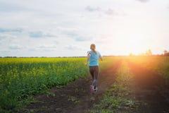 Женщина бегуна бежать на дороге в красивой природе Стоковое Фото
