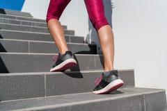 Женщина бегуна ботинок бега идя вверх по лестницам стоковые изображения rf
