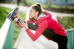 Женщина бегуна делая тренировки простираний Стоковые Изображения