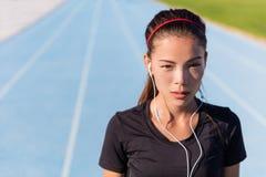Женщина бегуна слушая к, который побежали музыке с наушниками Стоковые Изображения