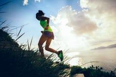 Женщина бежать вверх на лестницах горы взморья стоковая фотография rf
