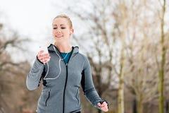 Женщина бежать вниз с пути на зимний день в парке стоковое фото rf