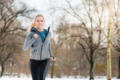 Женщина бежать вниз с пути на зимний день в парке стоковое фото