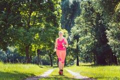 Женщина бежать вниз с пути на луге с гантелями веса стоковая фотография