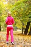 Женщина бежать в лесе осени.  Женская тренировка бегуна. Стоковые Изображения