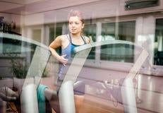 Женщина бежать в спортзале стоковое фото rf