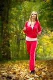 Женщина бежать в тренировке бегуна леса осени женской Стоковые Изображения RF