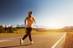 Женщина бежать горы прямой дороги outdoors стоковое фото rf