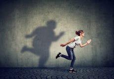 Женщина бежать далеко от ее тучной тени на стене стоковые изображения