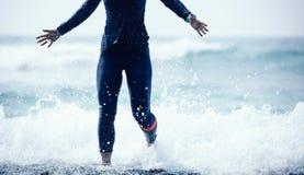 Женщина бежать и скача в seawaves стоковое фото