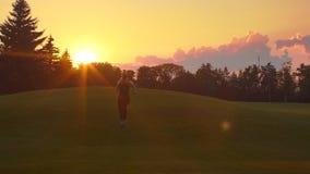 Женщина бежать назад на заходе солнца Заход солнца молодой женщины идущий Ход женщины фитнеса сток-видео