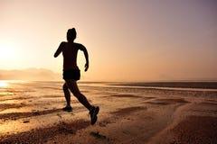 Женщина бежать на пляже восхода солнца Стоковая Фотография RF