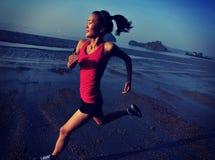 Женщина бежать на пляже восхода солнца Стоковые Изображения