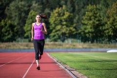 Женщина бежать на следе спорт стоковая фотография rf