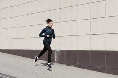 Женщина бежать около стены Стоковые Изображения