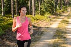 Женщина бежать через тренировку леса внешнюю стоковая фотография