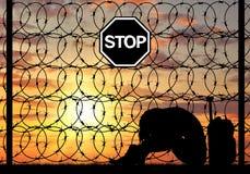 Женщина беженца отчаяния силуэта Стоковое фото RF