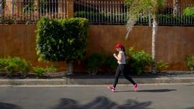 Женщина бежит вниз по улице среди пальм Здоровый активный образ жизни акции видеоматериалы