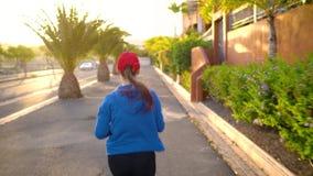 Женщина бежит вниз по улице среди пальм на заходе солнца, заднем взгляде Здоровый активный образ жизни сток-видео