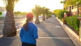 Женщина бежит вниз по улице среди пальм на заходе солнца, заднем взгляде Здоровый активный образ жизни акции видеоматериалы