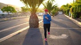 Женщина бежит вниз по улице среди пальм на заходе солнца Здоровый активный образ жизни акции видеоматериалы