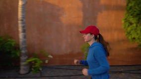 Женщина бежит вниз по улице среди тропического переулка Здоровый активный образ жизни сток-видео