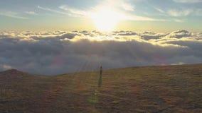 Женщина бежит над облаками к солнцу и краю горы и поднимая рук вид с воздуха акции видеоматериалы