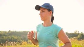 Женщина бежит outdoors на заходе солнца