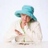 Женщина бедных зрелая думает о монетках в руке Стоковое фото RF