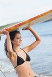 Женщина бикини держа surfboard надземный на пляже Стоковые Фото