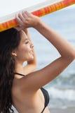 Женщина бикини держа surfboard надземный на пляже Стоковые Изображения RF
