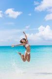 Женщина бикини потехи скача на пляж брызгая воду Стоковые Фотографии RF