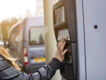 Женщина битника отжимая кнопку к оплачивать ne автопарковочного счетчика автомобиля Стоковые Фотографии RF