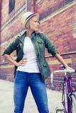 Женщина битника с винтажным велосипедом дороги на улице города Стоковые Фото