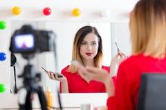 Женщина блоггера прикладывая косметики на камере Стоковое Изображение RF