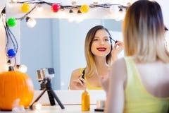 Женщина блоггера прикладывая косметики на камере Стоковые Фотографии RF
