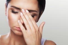 Женщина боли глаз красивая несчастная страдая от сильной боли глаза Портрет унылого женственного стресса чувства, касающая автоши стоковая фотография