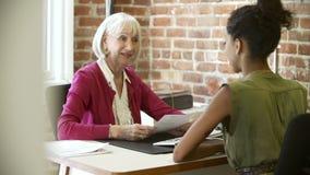 Женщина более старой коммерсантки интервьюируя более молодая в офисе сток-видео
