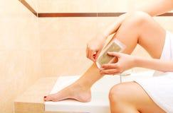 Женщина брея ее воск ноги стоковое изображение