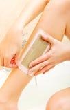 Женщина брея ее воск ноги стоковые изображения rf